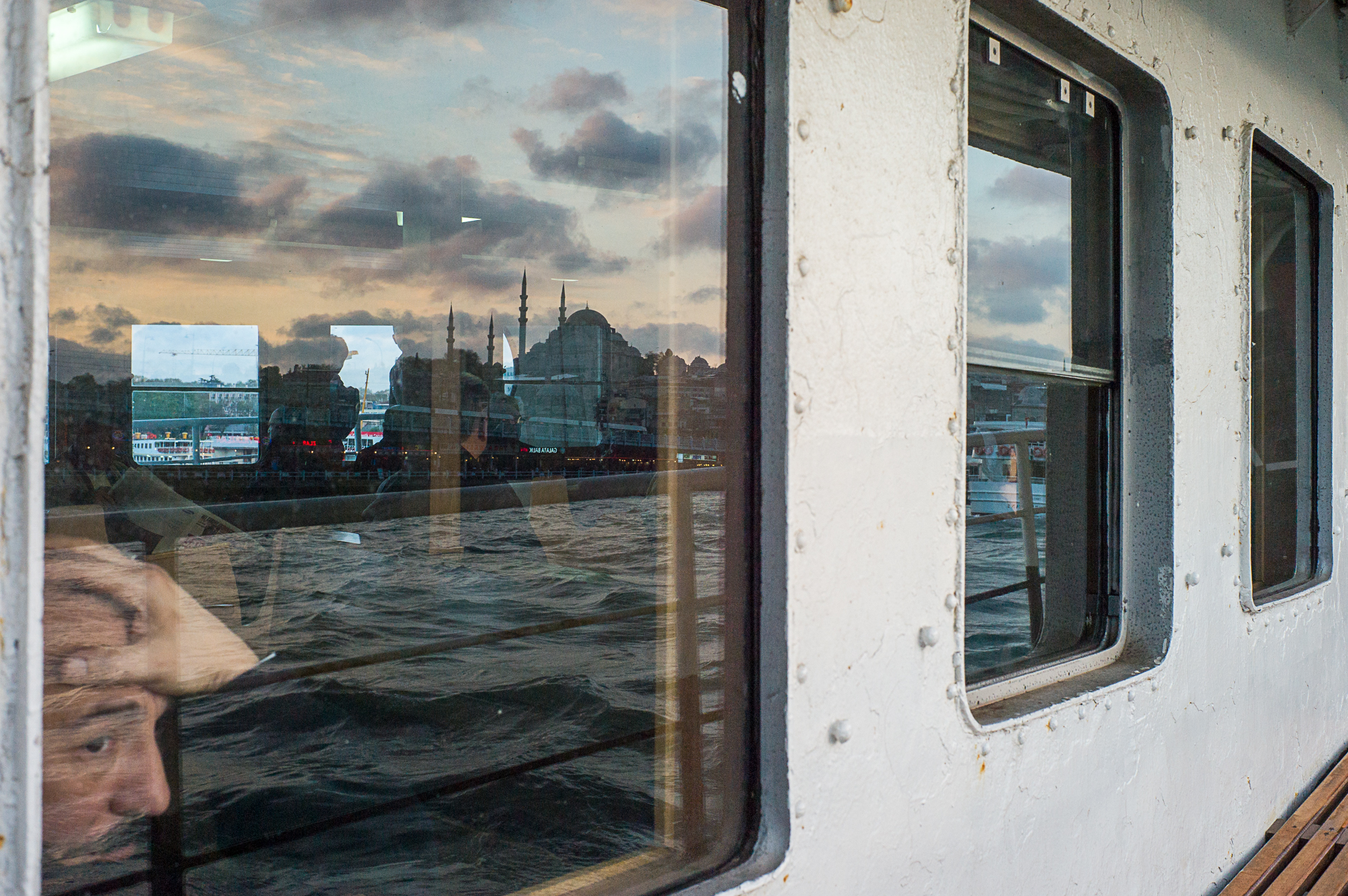 Reflection : A man is looking out of the window on a ferryboat, Istanbul