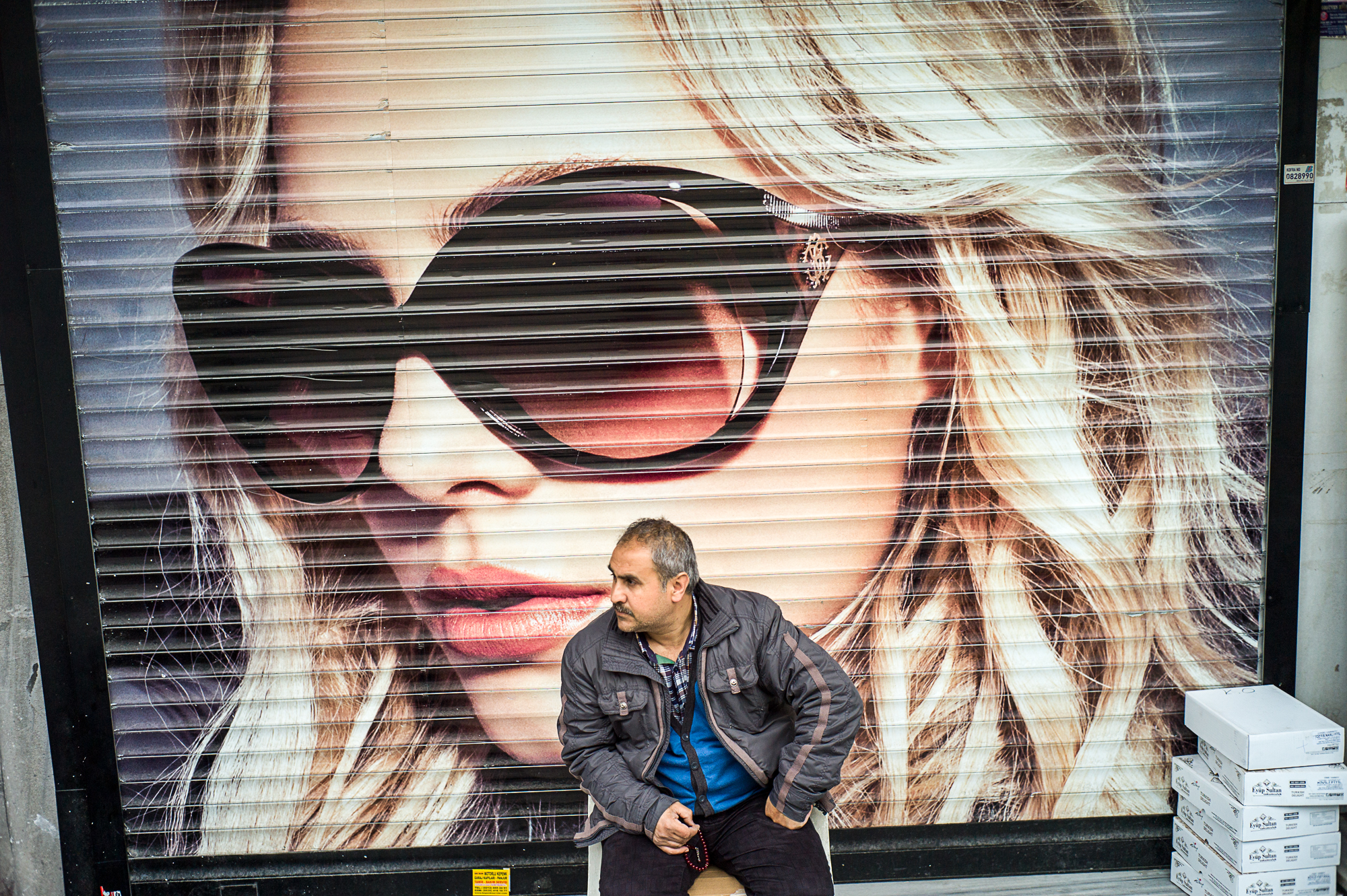 Sunglasses : A man is sitting in front of a shop, Istanbul