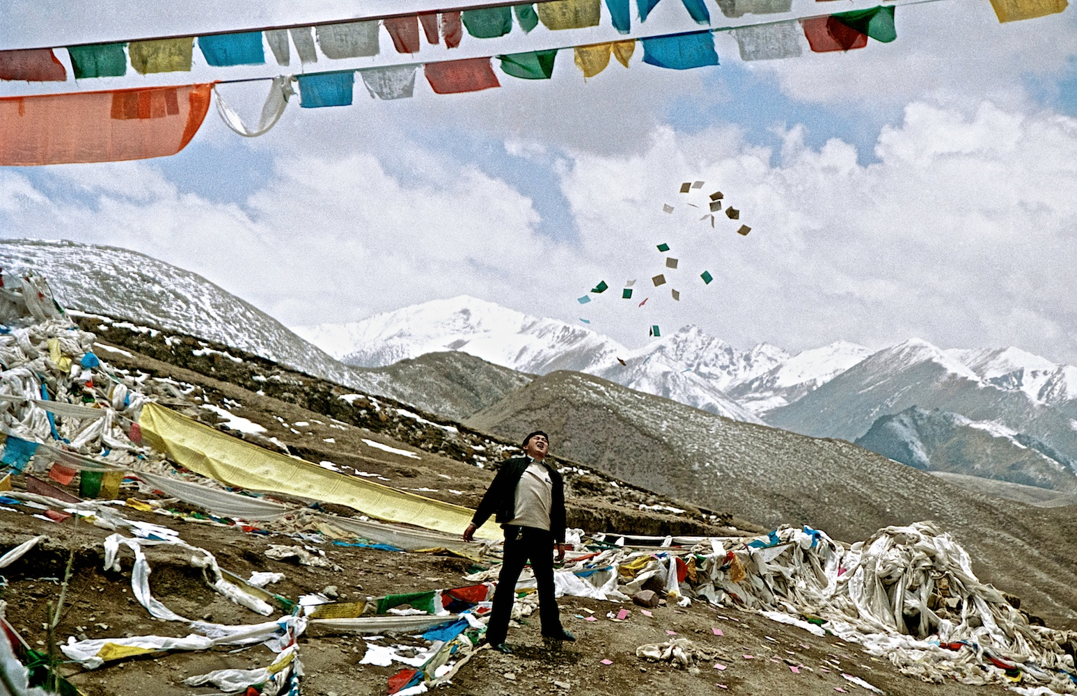 Tibet : Photo taken at a high pass on the Tibetan Plateau at about 5300mts above sea level, a mans trows praying flags in to the air.