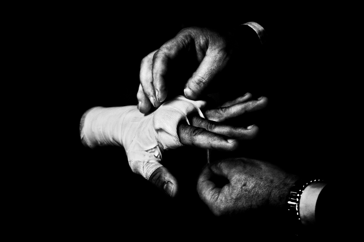 The fight : ITALY. Florence, 4th November 2011. Mandela Forum, the night of the match for the EBU (European Boxing Union) Welter Weight crown. Mr. Loreni, Leonard Bundu's agent, bandages athlete's hands.