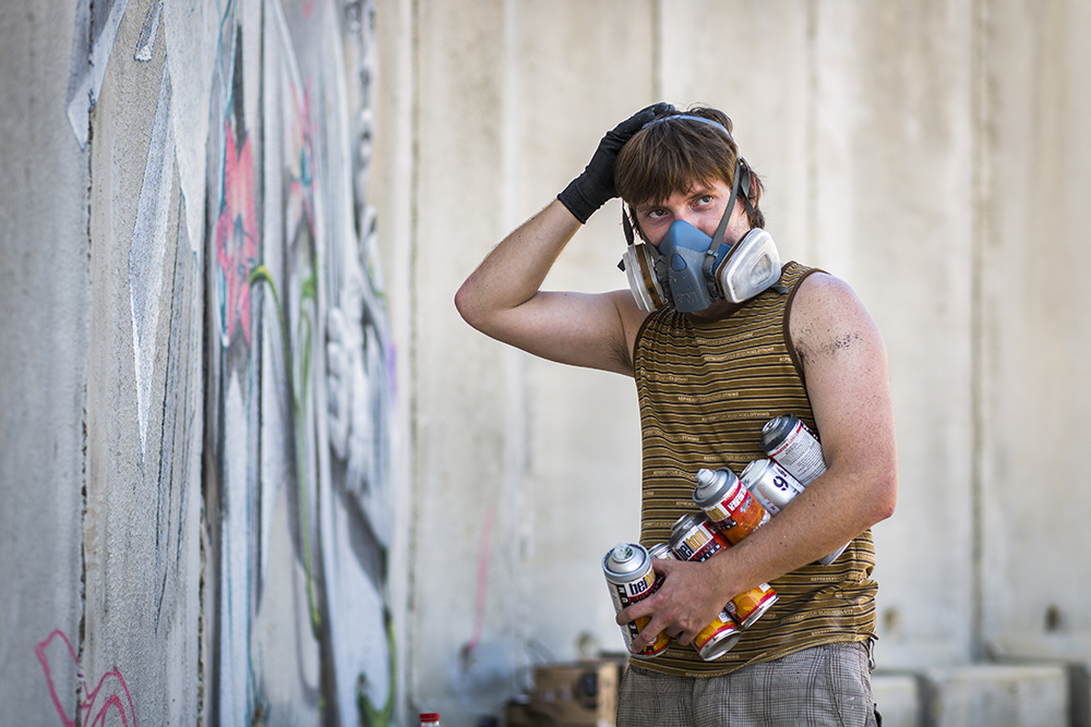 2. An Artist's Supplies : Artist, Chemis, prepares his piece with a protective mask and his cans of paint.