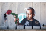 3. Painting Messages of Peace on a Security Fence : Artist, Mr. Dheo, paints a portrait of Artist 4 Israel's executive director, Craig, with messages of peace on a wall constructed from war.