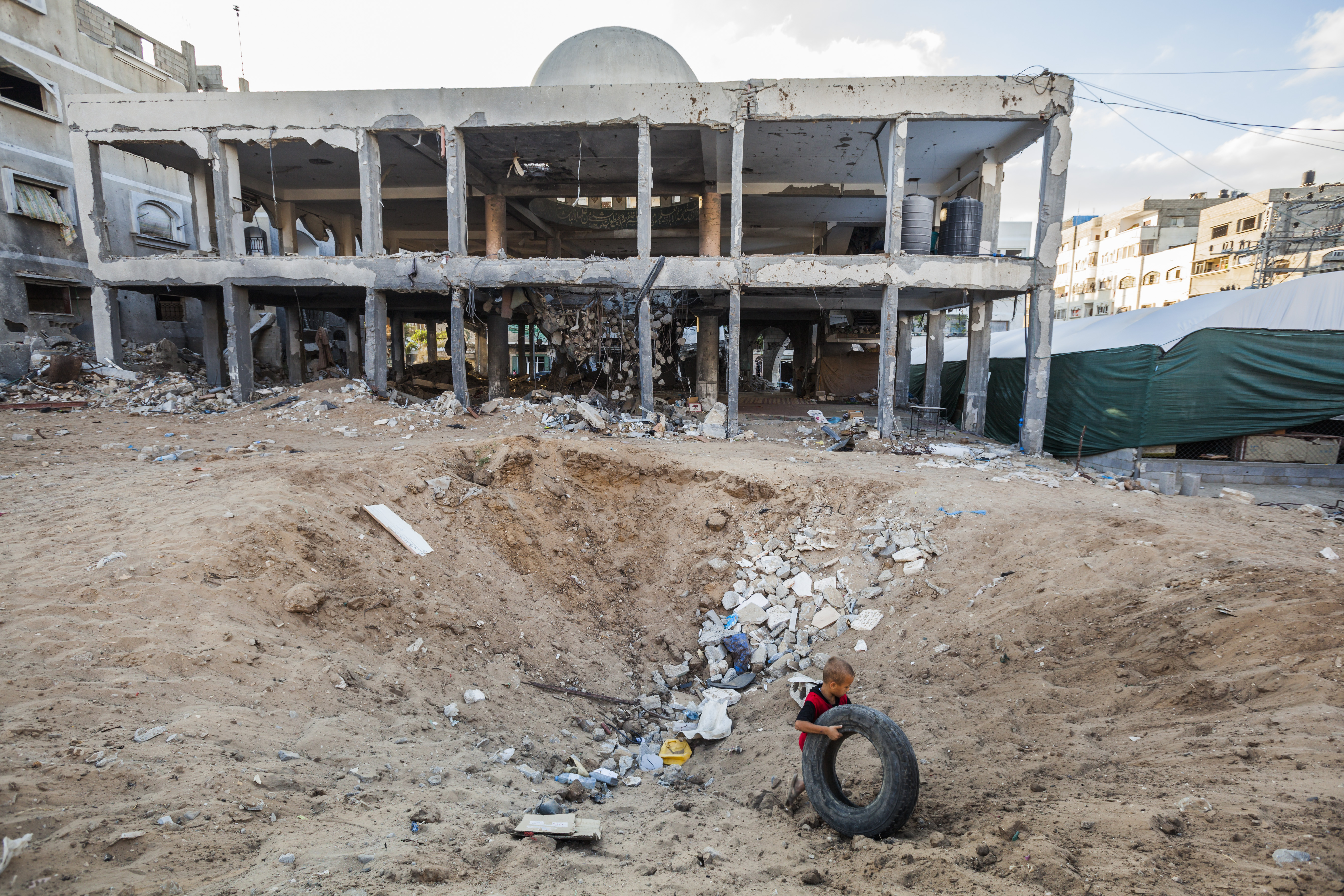 Destroyed mosques in Gaza after the last war against israel : Child plays with a tyre in a hole of a bomb close to the destroyed Al Susi mosque in Gaza city.