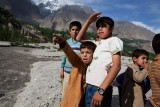 Paragliding Pakistan (5 of 7) : Young children from nearby villages watch on as the paraglider athletes prepare to land on a riverbank in Hunza, Pakistan.