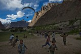 Paragliding Pakistan (6 of 7) : Children from the village of Hushé run in excitement as Belgium adventurer Tom De Dorlodot comes in for landing in Pakistan.