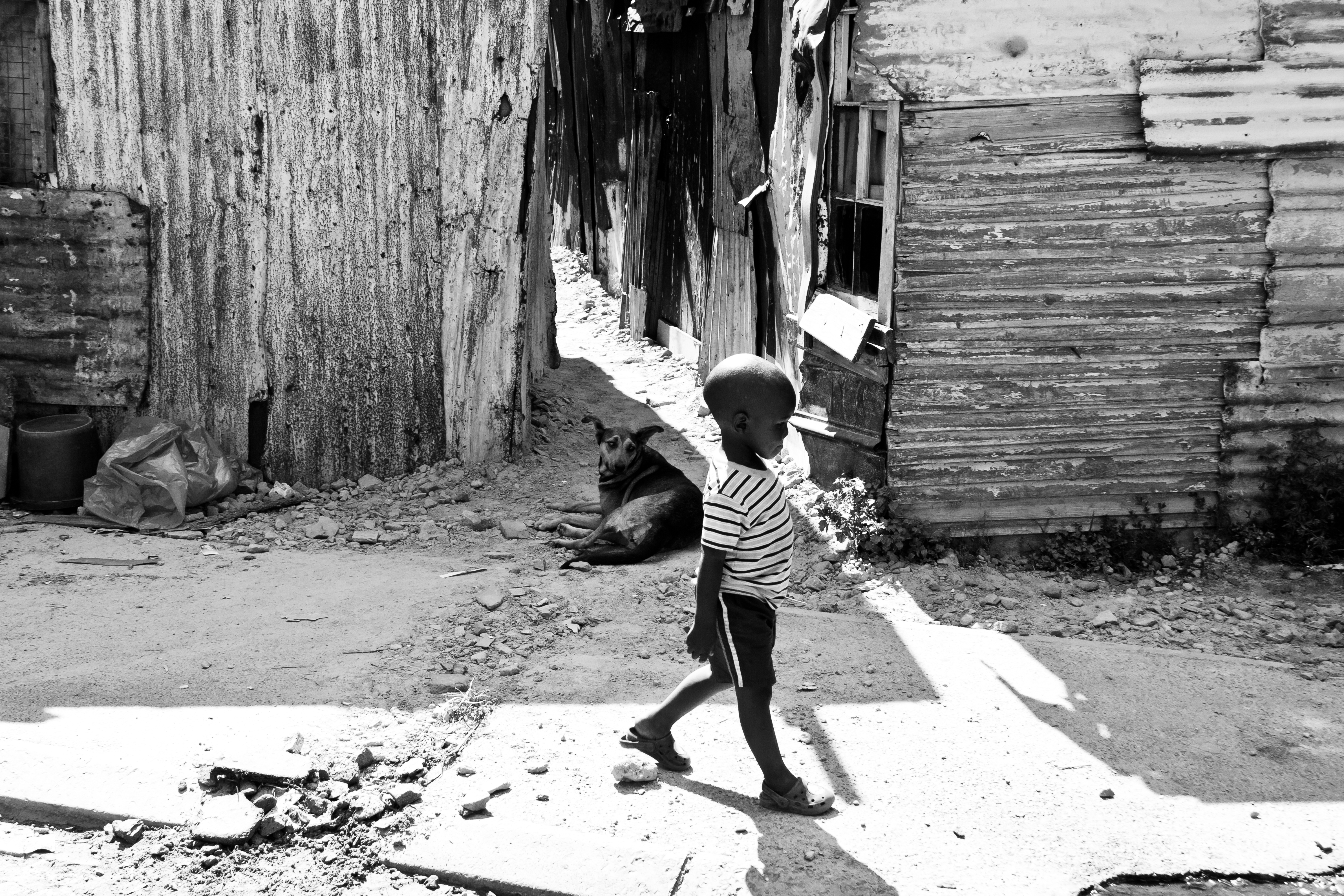 Untitled 3 : A boy walking along the dirt road through the shacks of Dunoon Township, South Africa