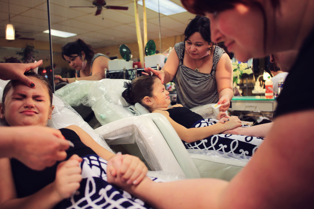Mary's Pageant : Mary Brunner, 8, holding her mothers hand as she gets her eyebrows waxed at the local nail and hair salon in Rochester, New York. Mary is preparing for the Angel Face Nationals pageant in Liverpool, NY.