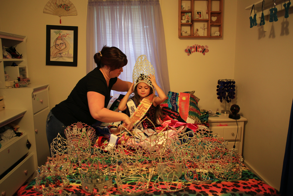 Mary's Pageant : Dana Brunner helps prepare her daughter Mary Brunner, 8, for a portrait in her bedroom surrounded by 57 crowns and sashes which she won at beauty pageants on October 18, 2012. Mary has been entering beauty pageants since the age of 5.