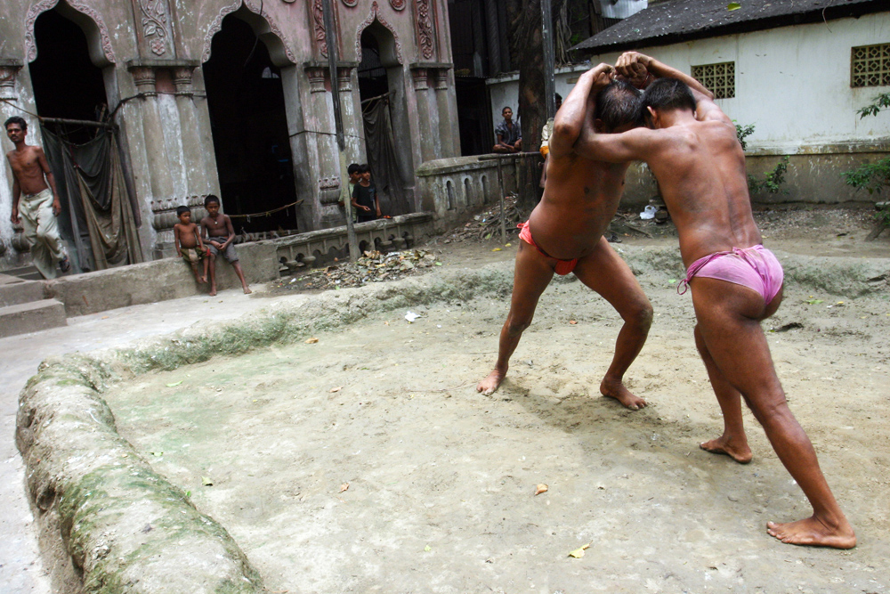 Indian Wrestler : Indian wrestlers practice wrestling beside holy river Ganges in Kolkata, India, July 06, 2006. Kushti is traditional Indian wrestling. It's not just a sport art, it's an ancient subculture. Wrestlers live and train together, have their strict rules. They may not drink, smoke and have sex. Their life must be pure. Kushti wrestlers live in gyms called akhara. Their diet consists of milk, eggs, almonds and home made bread called chapatis. Indian traditional wrestling is very popular for keeping strong and healthy body.