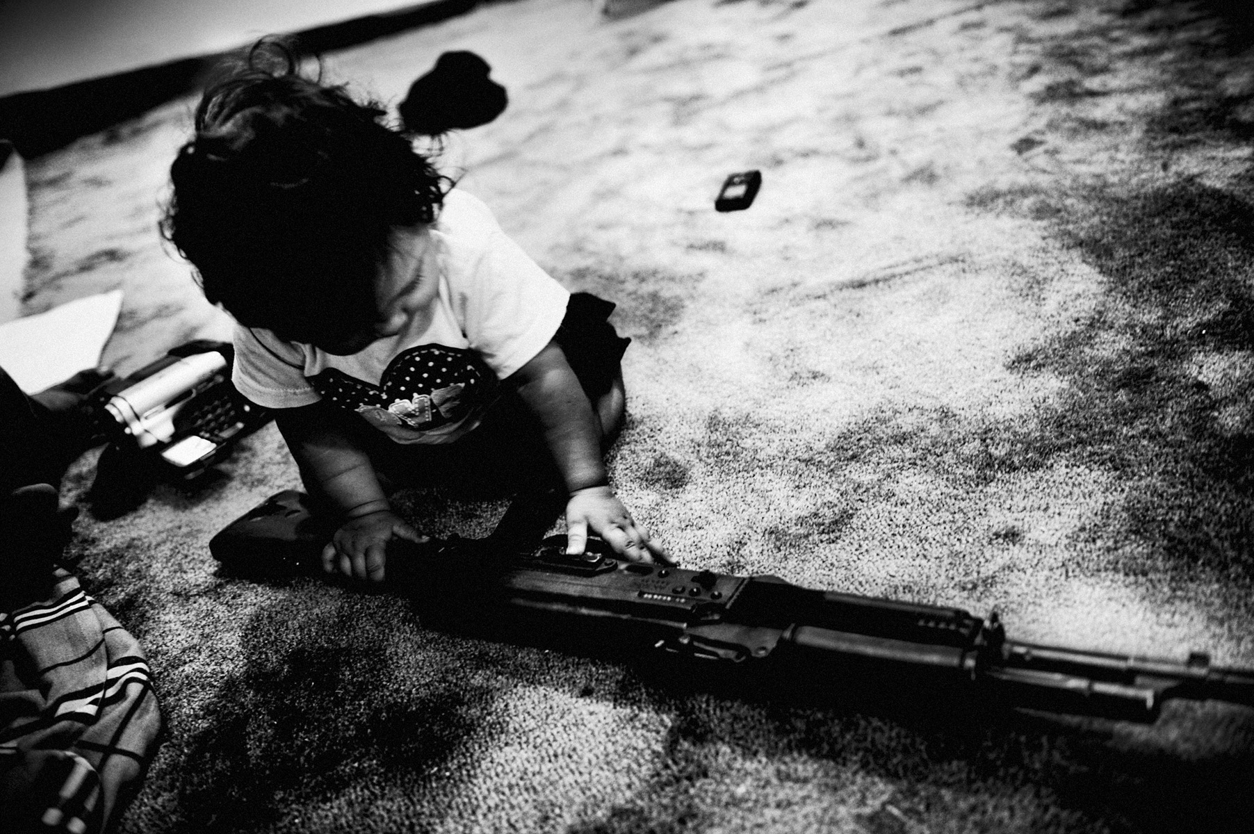 libya at the crossroads 7 : Dushka, the daughter of the only female soldier plays with her mum's gun