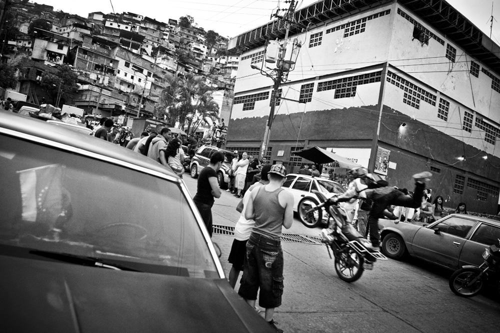 "03.- Moto Stunts : Motorcycle stunts perform in the middle of the street in ""El Valle"". Motorcycles are some of the most coveted objects and their robbery is at the origin of many murders every week."