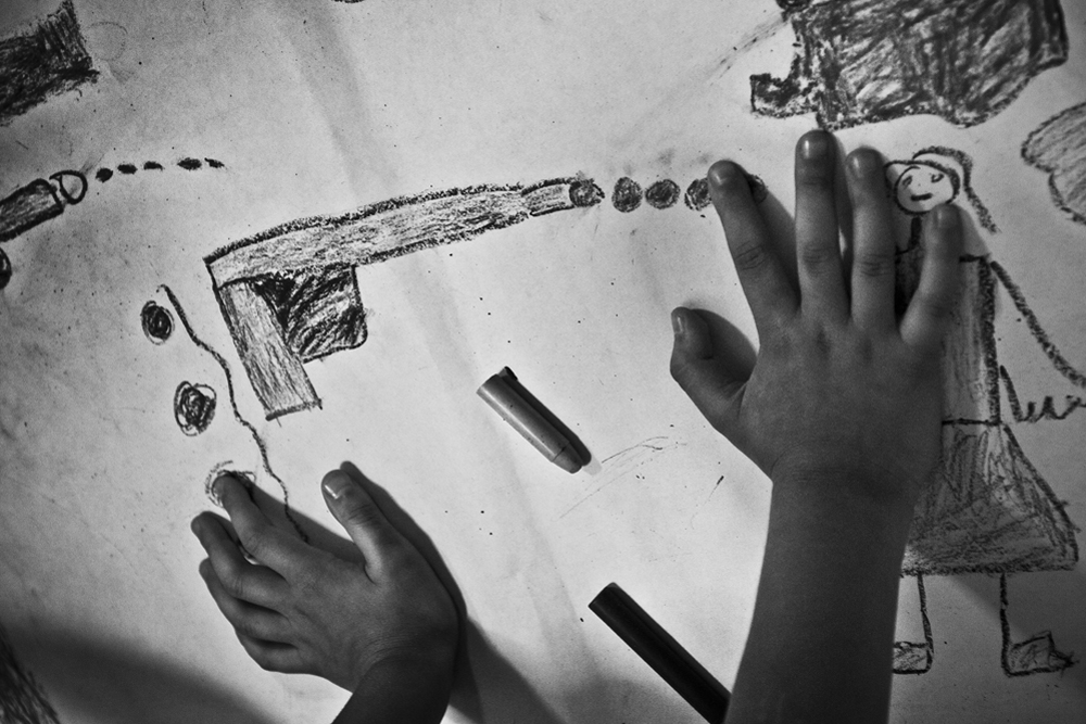 04.- Drawing violence. : In the outskirts of Caracas at a government workshop about violence and crime, a young kid draws daily scenes of violences in his community. The age of entry in crime life is dropping and there are more and more cases involving young boys of 12 or 13 years old.